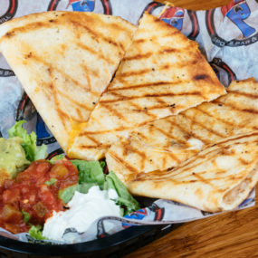 Quesadilla appetizer with Blackened chicken, tomato, and cheddar jack served with lettuce, salsa, guac and sour cream