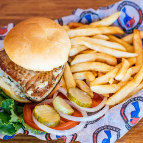 Blackened Tuna Sandwich with lemon dill aioli on a bun. Served with lettuce, tomato, onion, pickle and side of fries
