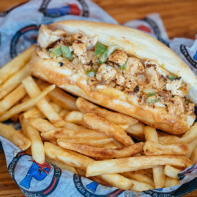 Chicken Cheesesteak sandwich prepared with onions, green peppers, and white America. Served on a toasted hoagie with Fries