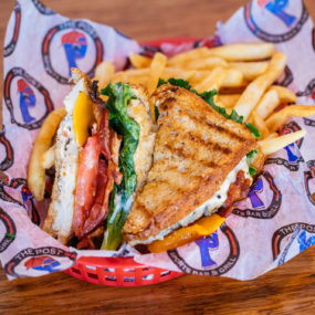 Chicken Club Sandwich with Grilled chicken breast topped with bacon, lettuce, tomato, cheddar & mayo. Served on grilled wheat