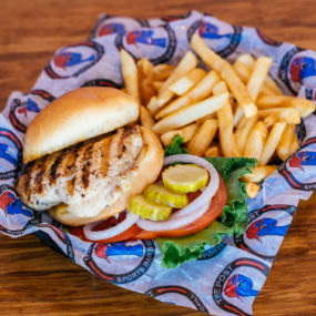 Grilled chicken sandwich with lettuce tomato, onion and side of fries