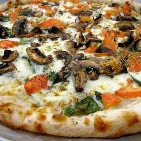 Pizza with Spinach, mozzarella, sautéed mushrooms, tomato and oregano sit atop an olive oil base pizza shell.