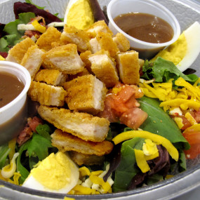 Chicken Club Salad with breaded chicken, bacon, egg, mixed greens, tomato, cheddarjack & croutons.  Served w/ranch