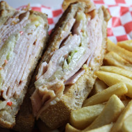 Turkey Reuben Sandwich with Smoked turkey, 1000 island dressing, cole slaw, and swiss served on grilled wheatbread