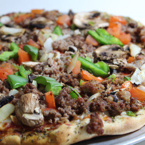 Pizza with pepperoni, sausage, hamburger, mushroom, tomato, green pepper and onion.