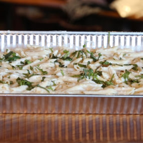 Penne pasta catering tray topped with homemade alfredo sauce, with or without blackened chicken