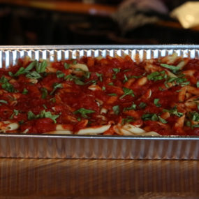 Penne pasta catering tray topped with a homemade marinarasauce, with or without meatballs.