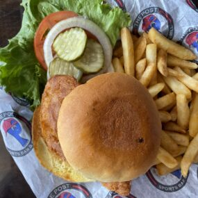 Fried Fish sandwich on a bun with fries and lettuce tomato and onion on The Post Sports Bar & Grill sheet paper