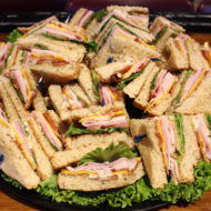 Club Sandwich catering tray with Smoked turkey, sliced ham, bacon, lettuce, tomato, cheddar & mayo on whole wheat bread