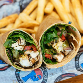 Pesto chicken wrap with spring mix & roasted red peppers & pesto served in a wheat tortilla with fries