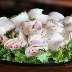 Turkey gouda BLT wrap Catering Tray with bacon, spinach, tomato, smoked gouda & cranberry mayo inside a wheat tortilla