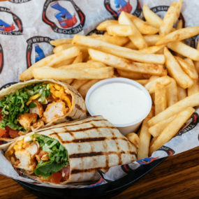 Buffalo chicken wrap with Breaded chicken tossed in hot sauce, lettuce, tomatoes, cheddar jack, & ranch inside a white tortilla with side of fries
