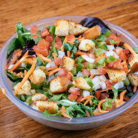 House salad catering tray with mixed greens topped with tomato, onion, green pepper, carrot, and croutons
