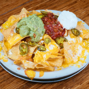 Nachos Grande Appetizer with Homemade corn chips, jalapenos, melted cheddar jack, guac, sour cream and salsa